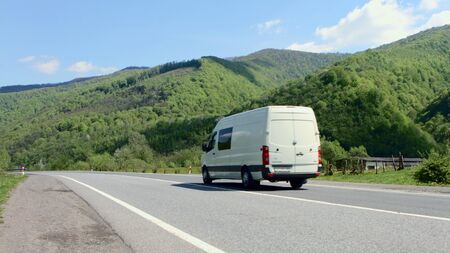 White van traveling at speed on the roads against the backdrop of mountains and pure summer sky Фото со стока