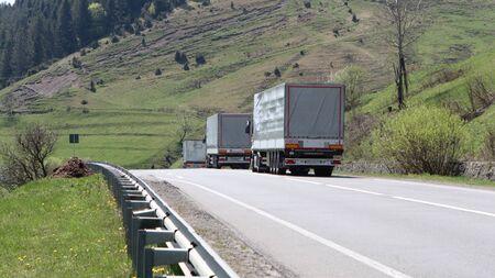 Three cargo truck go on road Фото со стока
