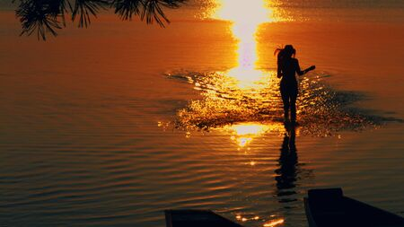Beautiful young girl running on water against the background of sunset.