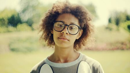 Young pensive beautiful woman with glasses closeup simulates happiness. Park, summer sunny day. Stock fotó