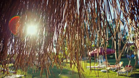 Wicker sunshade with sun flare on the beach. Bright sun lit by hanging dry reeds.