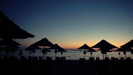 Beach umbrellas silhouettes in front of sea, evening sky. Steadicam shot.