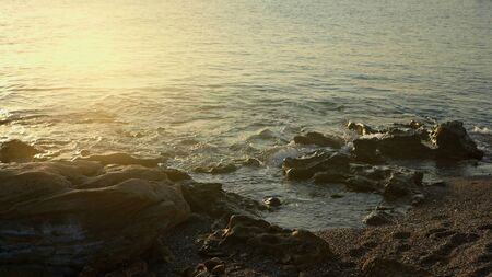 Fantastic view of the seashore at sunset. Easy soft light falling on rocks and water. Sunset over sea Фото со стока