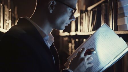 A young man with a flashlight at night looking documents in libraries Фото со стока
