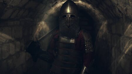 Medieval knight in the armor with the sword and shield. Artistic toning Фото со стока