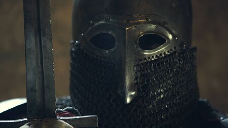 Close up on face of medieval knight face and sword Фото со стока