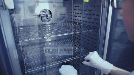 Female putting test tubes in incubator