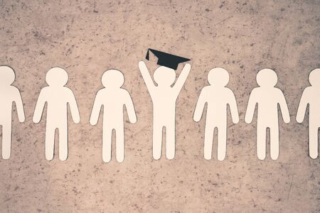 White paper figures of people stand in line. In center is silhouette of University graduate with hat on his head. A symbol of education and the beginning of career.
