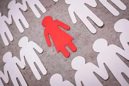 The pink paper figure of a girl stands alone. White silhouettes of men holding hands around her.A symbol of discrimination and sexism. Non-acceptance into the team.
