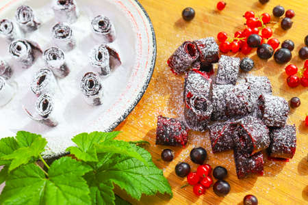 Homemade dried fruit rolls in powdered sugar. Natural eco food made from fresh currant berries. concept of healthy nutrition, detoxification and natural sweets.