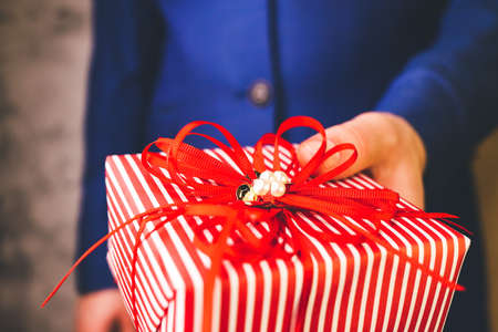 man in blue suit holds out gift box wrapped in white and red paper with bow.