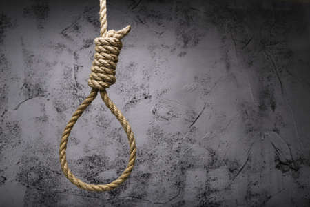 brown rope knot around neck hanging on old gray wall background, emotional stress and concept of suicide.