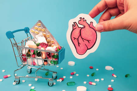 Treatment or prevention of heart diseases with variety of pills. pencil draw of human heart in hand against background of many colorful pills in grocery cart. turquoise background. Imagens