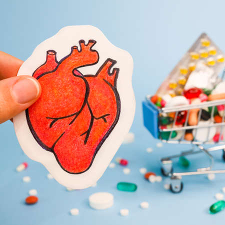 Treatment or prevention of heart diseases with variety of pills. pencil draw of human heart close-up in fingers against background of many colorful pills in trolley cart. Blue background. square image