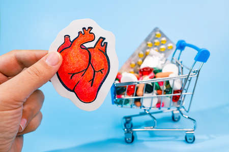 Treatment or prevention of heart diseases with variety of pills. pencil draw of human heart in hand against background of many colorful pills in grocery cart. Blue background.