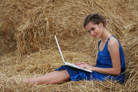 wisp: Country girl with laptop sitting at haystack looking to camera