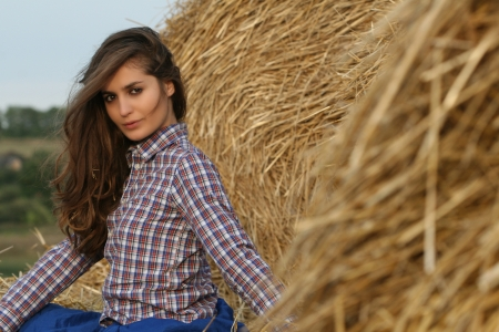 Country girl sitting at haystack half-turned looking to camera photo