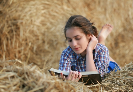 Country girl reading book lying at haystack photo
