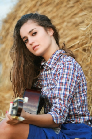 Country girl with guitar sitting at haystack looking to camera photo
