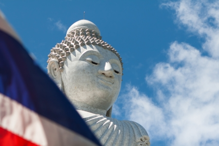 thai flag covers buddha stone sculpture over the blue sky background photo