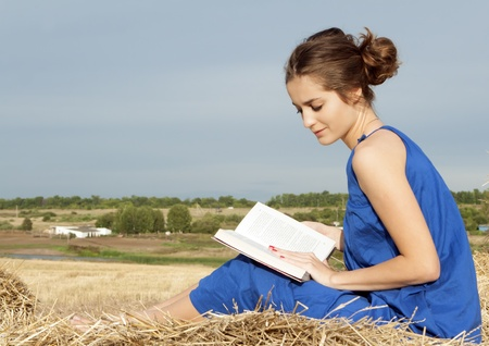 25 years old: 25 years old woman reading book outdoors on hay