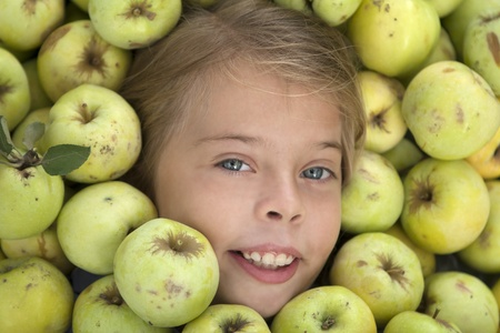 7 years old: 7 years old girl face in green apples mass Stock Photo