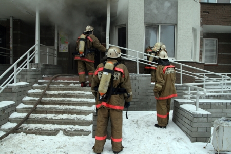 buiding: firefighters at smoking buiding entrance