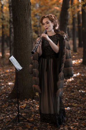 Young woman playing oboe against musical stand in park Stock Photo
