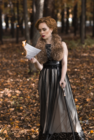 Young attractive woman standing in fall park and looking to burning musical notes in her hand, leaning on cane