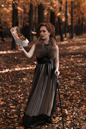 cane collar: Young attractive woman standing in fall park and holding burning musical notes in hand, leaning on cane