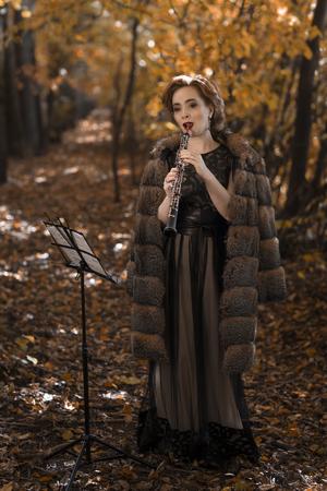 clarinete: Mujer joven que juega contra el oboe soporte musical en el parque Foto de archivo