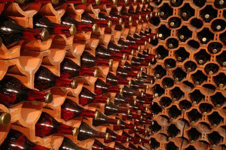 Racks with bottles in a dark wine cellar photo