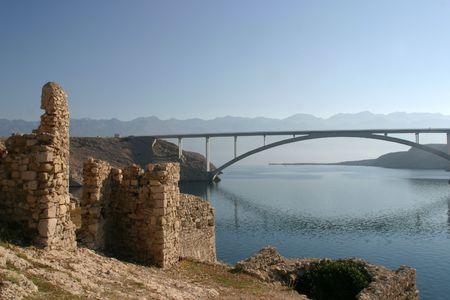 Ancient ruins and bridge over the sea photo