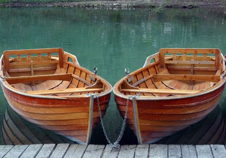 row boat: Rowboats parked in a row near a clear water lake