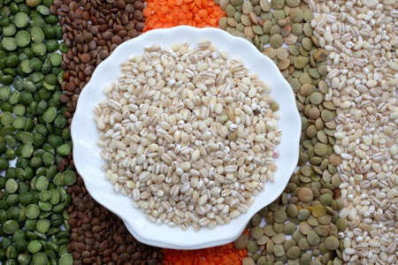 Ceramic plate with pearl barley over seeds and grains background Stock Photo - 8867386