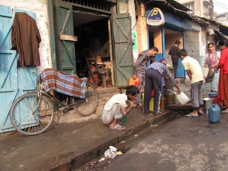 KOLKATA, INDIA -JANUARY 23: Streets of Kolkata. People filling up water in cans, January 23, 2009.                           Stock Photo - 10581015