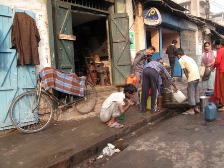 poverty india: KOLKATA, INDIA -JANUARY 23: Streets of Kolkata. People filling up water in cans, January 23, 2009.