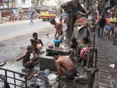kolkata: KOLKATA, INDIA -JANUARY 25: Streets of Kolkata. Indian people wash themselves on a street , January 25, 2009.