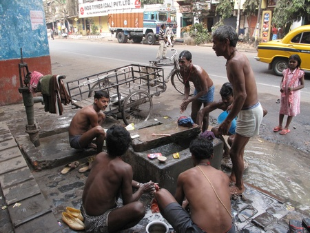 calcutta: KOLKATA, INDIA -JANUARY 25: Streets of Kolkata. Indian people wash themselves on a street , January 25, 2009.