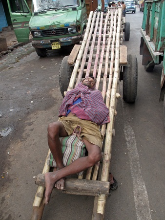 Kolkata, INDIA - JANUARY 25: Indian man asleep waiting for customers to transport their cargo on January 25, 2009, in Kolkata. These men are one of the hardest working and also poorest in the whole India.