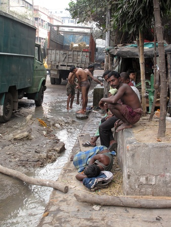 KOLKATA, INDIA -JANUARY 25: Streets of Kolkata. Indian people wash themselves on a street , January 25, 2009.