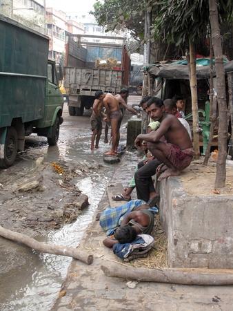 KOLKATA, INDIA -JANUARY 25: Streets of Kolkata. Indian people wash themselves on a street , January 25, 2009.