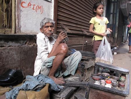 KOLKATA, INDIA -JANUARY 25: Streets of Calcutta. Shoe shiner waiting for a customer on January 25, 2009.