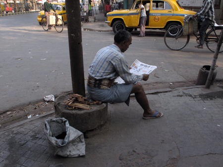 KOLKATA, INDIA - FEBRUARY 03: Streets of Kolkata, man reading the newspaper while ignoring everything around him, in Kolkata- India on February 03, 2009.