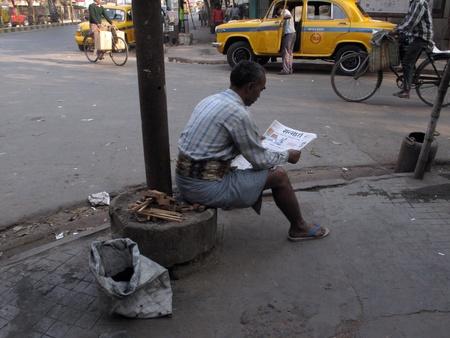 KOLKATA, INDIA - FEBRUARY 03: Streets of Kolkata, man reading the newspaper while ignoring everything around him, in Kolkata- India on February 03, 2009.