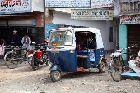 kilometraje: KUMROKHALI, INDIA - 12 de enero: Auto rickshaw taxis en una carretera en Kumrokhali, Bengala Occidental, India, 12 de enero de 2009. Kilometraje t�pico de un rickshaw auto fabricados en la India se encuentra a 35 kil�metros por litro de gasolina.