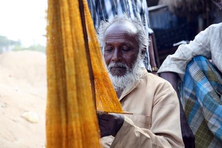 india fisherman: KUMROKHALI, INDIA - JANUARY 12: portrait of a fisherman who weaves a fishing net before the next fishing, January 12, 2009 in Kumrokhali, West Bengal, India.