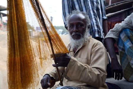 KUMROKHALI, INDIA - JANUARY 12: portrait of a fisherman who weaves a fishing net before the next fishing, January 12, 2009 in Kumrokhali, West Bengal, India. Stock Photo - 10770220