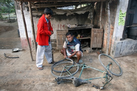 KUMROKHALI, INDIA - JANUARY 12: Mechanic in the workshop repair the tire on a bicycle. The bicycle is in India, one of the main means of transport., Kumrokhali, West Bengal on January 12, 2009.