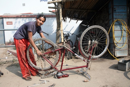BARUIPUR, INDIA - JANUARY 13: Mechanic in the workshop repair the tire on a bicycle. The bicycle is in India, one of the main means of transport., Baruipur, West Bengal on January 13, 2009.